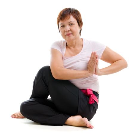 senior yoga: Asian senior woman practicing yoga, isolated on white background. Stock Photo