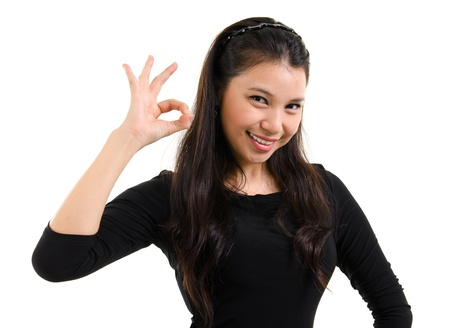 Pretty young woman showing okay hand sign with great smile standing isolated on white background photo