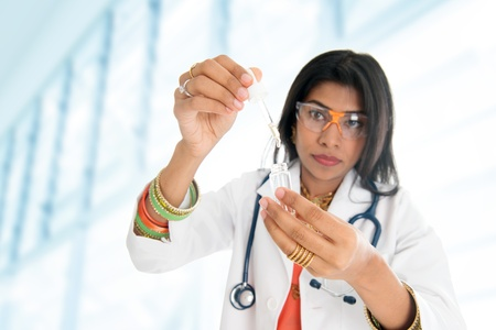 scientists: An Indian female scientific researcher holding at a liquid solution in a lab. Stock Photo