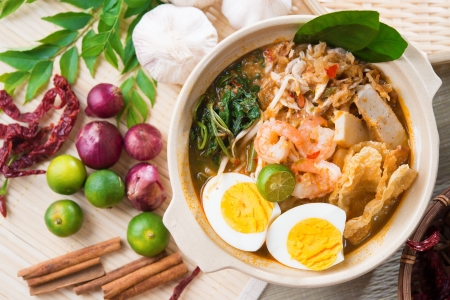 Singapore prawn noodles or prawn mee. Famous Singaporean food spicy fresh cooked har mee in clay pot with hot steam. Asian cuisine. photo