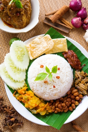 Nasi lemak kukus traditional malaysian spicy rice dish, fresh cooked with hot steam. Served with belacan, ikan bilis, acar, peanuts and cucumber. Decoration setup. photo