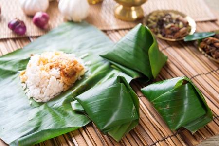 Nasi lemak, popular traditional Malaysia food wrapped with banana leaf. Stock Photo - 20620146