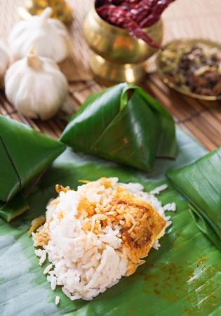 nasi: Nasi lemak Malay dish, popular traditional Malaysian food wrapped with banana leaf.