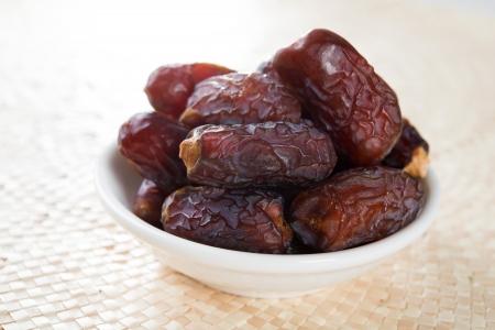 Kurma gedroogd dadelpalm vruchten, ramadan voedsel dat gegeten in vastenmaand. Stapel van verse gedroogde datum vruchten in kom.