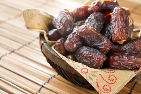 Dried date palm fruits or kurma, ramadan food which eaten in fasting month. Pile of fresh dried date fruits ready to eat in bamboo basket. photo
