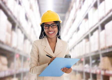 Smiling Indian woman doing stock tick in warehouse  with safety helmet smiling happy writing report. Portrait of beautiful Asian female model standing inside factory. photo