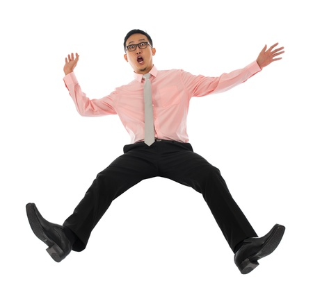 backwards: Full body shocked young Asian businessman falling backwards open arms, isolated on white background