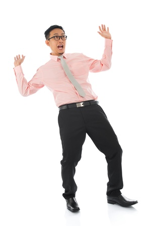 horrified: Full body shocked young Asian businessman open arms body bend backwards, isolated on white background