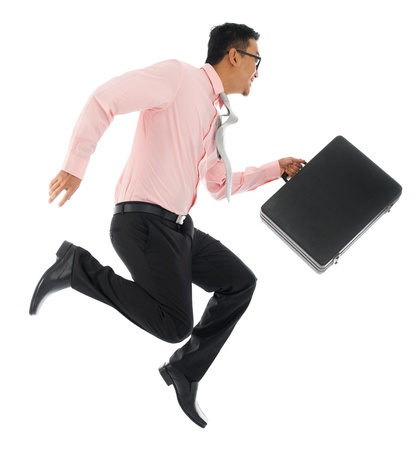 Full body young Asian businessman running or jumping up with a briefcase, isolated on white background photo