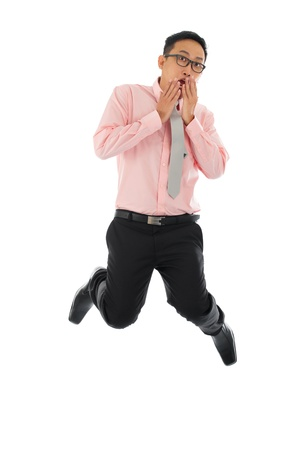 businessman jumping: Full body young Asian businessman get shock, hands covering mouth and jumping up  isolated on white background Stock Photo