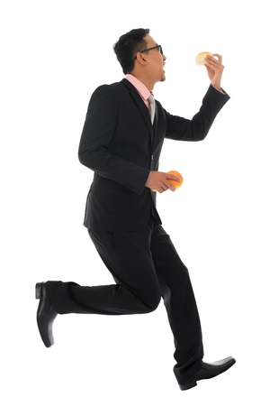 Full body Asian businessman in hurry eating bun and running, isolated on white background photo