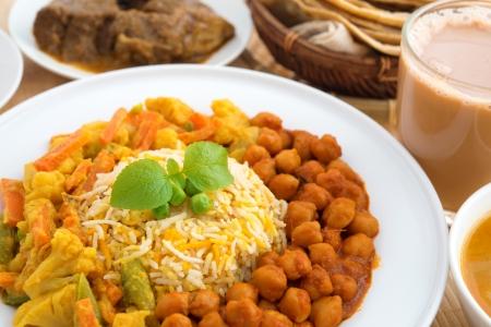 mutton: Indian food biryani rice, mutton curry, chapatti, milk tea and dal. Indian dining table.