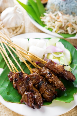 singapore culture: Satay or sate, skewered and grilled meat, served with peanut sauce, cucumber and ketupat. Traditional Malay food. Delicious hot and spicy Malaysian dish, Asian cuisine.