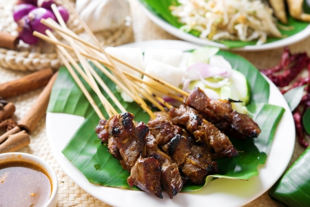 malay food: Satay or sate, skewered and grilled meat, served with peanut sauce, cucumber and ketupat, Malaysia or Indonesia food. Traditional Malay food. Hot and spicy Malaysian dish, Asian cuisine.