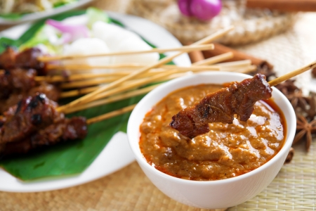 satay sauce: Satay or sate, skewered and grilled meat, served with peanut sauce, cucumber and ketupat. Traditional Malay food. Malaysian dish, Asian cuisine. Stock Photo