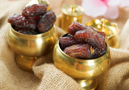 middle eastern food: Dried date palm fruits or kurma, ramadan food which eaten in fasting month. Pile of fresh dried date fruits in golden metal bowl.