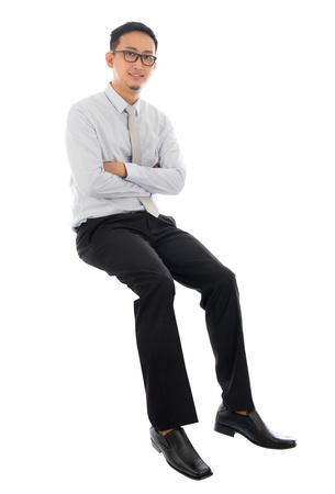 Full body Asian businessman sitting on a transparent block, isolated on white background. Asian male model. photo