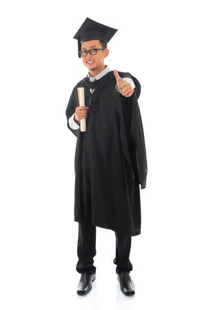 Full body Asian male university student in graduation gown thumb up isolated on white background photo