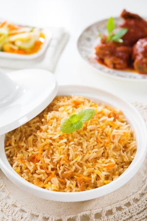 biryani: Biryani rice or briyani rice, curry chicken and salad, traditional indian food on dining table.