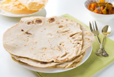 Chapatti roti or Flat bread, papadom and curry dhal. Indian food on dining table.  photo