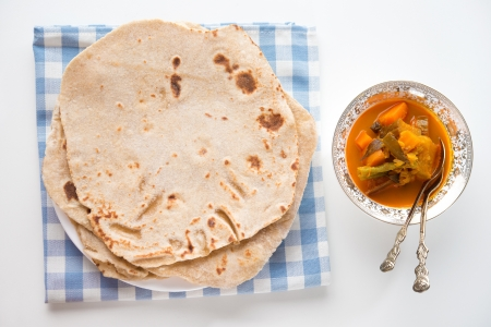 Chapatti roti or Flat bread and curry dahl. Indian food on dining table.  photo