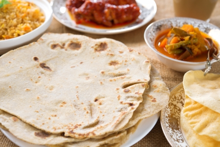 Chapatti roti or chapati, curry chicken, biryani rice, salad, masala milk tea and papadom. Indian food on dining table.  photo