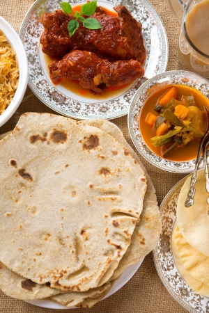 tarik: Chapatti roti, curry chicken, biryani rice, salad, masala milk tea and papadom. Indian food on dining table.
