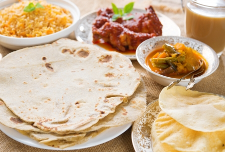 Chapatti roti or Flat bread, curry chicken, biryani rice, salad, masala milk tea and papadom. Indian food on dining table.  photo