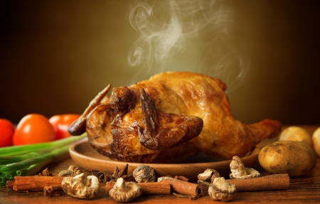 oven chicken: Whole roasted chicken with vegetables, on wooden tray fresh from oven with hot steam smoke, brown background