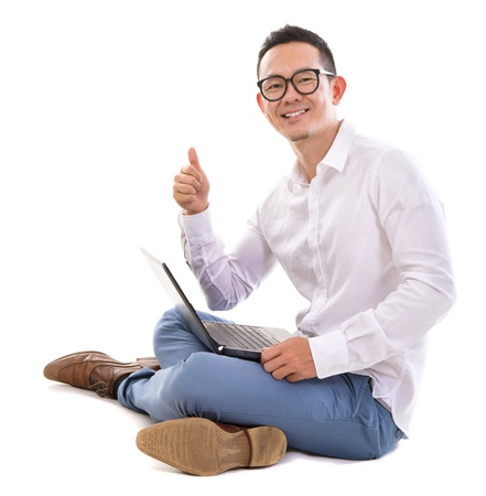 asian laptop: Full length of happy thumb up Asian businessman using laptop sitting over  white background