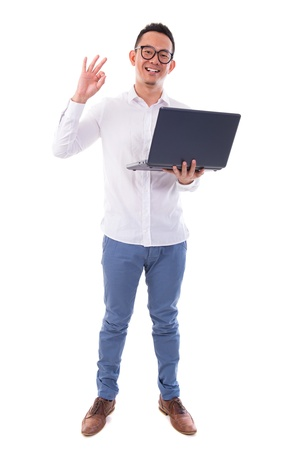 the whole body: Full length of happy Asian businessman using laptop showing okay hand sign standing isolated over  white background Stock Photo