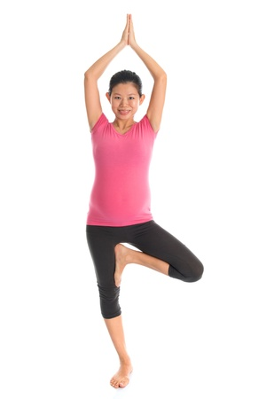 Prenatal yoga. Full length healthy Asian pregnant woman doing yoga exercise stretching at home, fullbody isolated on white background. Yoga positions standing tree pose. photo