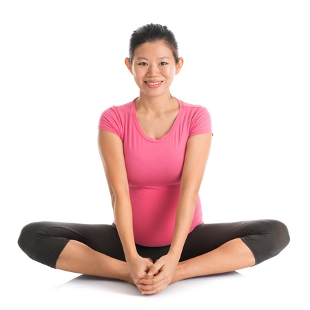 Prenatal yoga. Full length healthy Asian pregnant woman doing yoga exercising stretching, fullbody isolated on white background. Yoga butterfly pose. photo