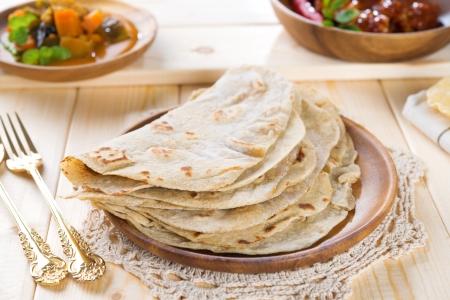 curry: Chapati o roti pan plano, pollo al curry y lentejas. Comida india en la mesa de comedor.
