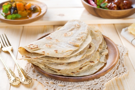 Chapatti roti or Flat bread, curry chicken and dhal. Indian food on dining table. photo