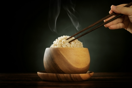 Cooked organic basmati brown rice in wooden bowl with human hand chopsticks and hot steam smoke on dining table. Low light setting. Stock Photo