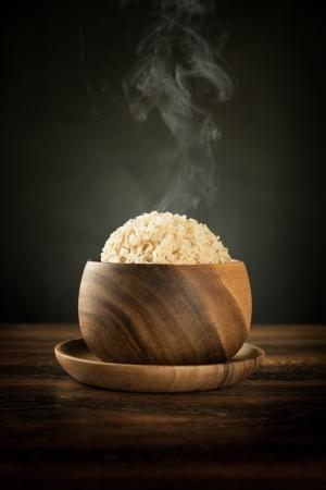 식탁에 뜨거운 증기 연기와 나무 그릇에 요리 유기 스마티 현미. 낮은 조명 설정.