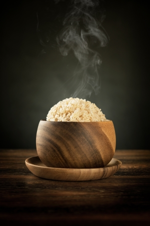 basmati: Cooked organic basmati brown rice in wooden bowl with hot steam smoke on dining table. Low light setting. Stock Photo
