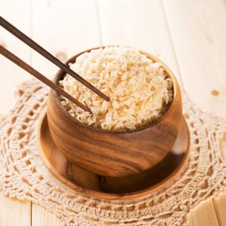 marrón: Close up de arroz basmati cocido orgánico marrón en un tazón de madera con los palillos en la mesa de comedor.