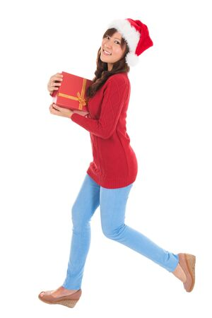 Beautiful Christmas woman running and holding gift wearing Santa hat. Standing in full body isolated on white background. Smiling woman portrait of a beautiful Asian model. photo