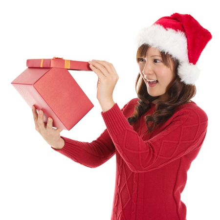 Christmas Gift - Asian woman opening gift surprised and happy, Young beautiful smiling woman in Santa hat. Funny cute photo of Asian woman isolated on white background photo