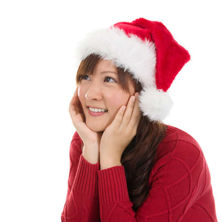 Thoughtful Asian Christmas woman wearing santa hat. Christmas woman portrait of a cute, beautiful smiling Asian Chinese  Japanese model. Isolated on white background. photo
