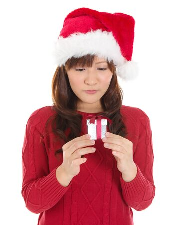 Christmas Gift - Asian woman looking at small gift disappointed and unhappy. Young woman in Santa hat. Funny cute photo of Asian woman isolated on white background. photo