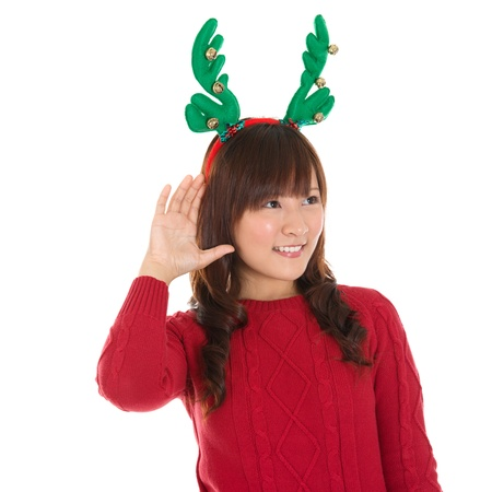 Young Asian Christmas Girl listening isolated on white background, Asian female model. photo