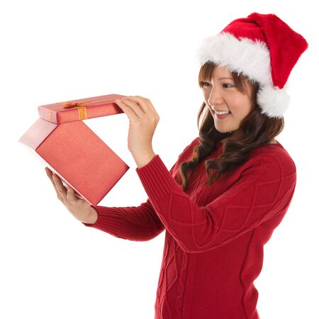Christmas Gift - Asian woman opening gift happy face, Young beautiful smiling woman in Santa hat. Funny cute photo of Asian woman isolated on white background photo