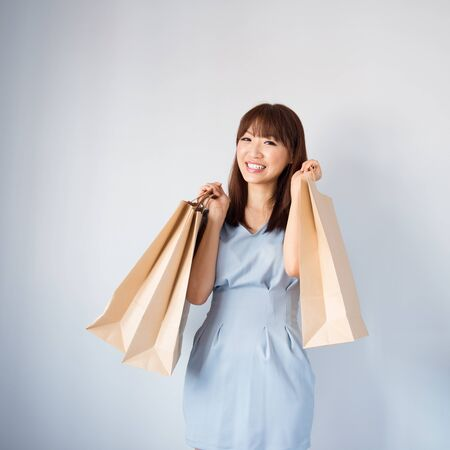 Shopping woman holding shopping bags looking at camera on blue background. Beautiful young Asian shopper smiling happy. photo
