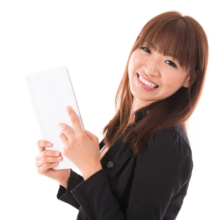 Portrait of happy Asian woman using a tablet pc isolated on white background. Asian female model. photo