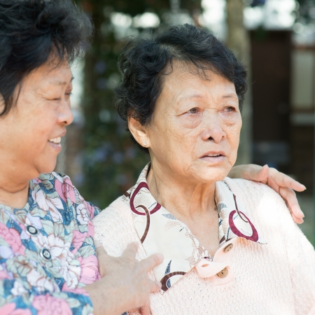 Asian mature woman consoling her crying old mother at outdoor natural green park.  photo