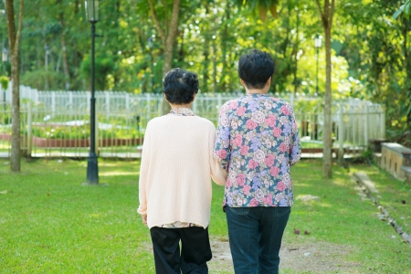 senior living: Rear view of Asian 80s old mother and 60s senior daughter holding hands walking at outdoor park.