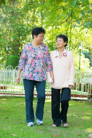 Asian 80s old mother and 60s senior daughter holding hands walking at outdoor park. photo